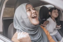 Muslim Lady Dancing Happily in Her Car royalty free stock image