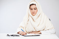 Muslim lady doctor writing documents Royalty Free Stock Images