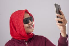 Muslim Lady in Red Smiling and Taking Selfie Picture of Her Self on Phone royalty free stock photos