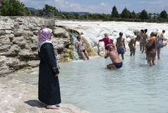 A Muslim lady watches tourists as they relax in one of the man-made thermal pools at Cotton Castle in Pamukkale, Turkey. Cotton Castle, also referred to as the royalty free stock images