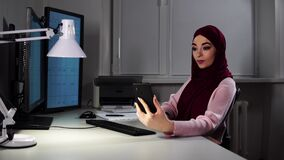 Muslim lady works at office when somebody calls her on smartphone