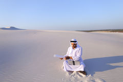 Muslim male architect sitting with laptop on sand in desert on h Stock Photo