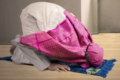 Muslim male posing prostration at home Stock Photos