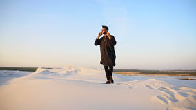 Muslim male tourist speaks on phone and shares news, standing in middle of sandy desert on hot summer evening. Young fellow Arabian traveler calls on mobile stock video