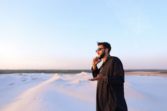 Muslim male tourist speaks on phone and shares news, standing in Royalty Free Stock Images