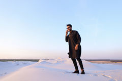 Muslim male tourist speaks on phone and shares news, standing in Stock Photography