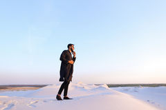 Muslim male tourist speaks on phone and shares news, standing in Royalty Free Stock Photo