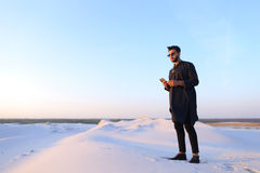 Muslim male tourist speaks on phone and shares news, standing in Stock Photos