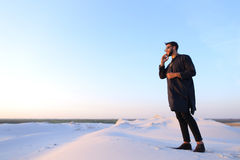 Muslim male tourist speaks on phone and shares news, standing in Royalty Free Stock Photos