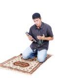 Muslim man är holdingjärnekboken Qoran och att be royaltyfria foton