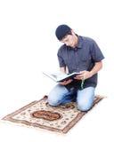 Muslim man är holdingjärnekboken Qoran och att be arkivbilder