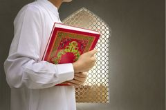 Muslim man bringing the Koran on his hand Royalty Free Stock Image