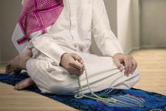 Muslim man dhikr with beads at home Stock Photos