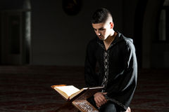 Muslim Man In Dishdasha Is Reading The Quran Stock Photography