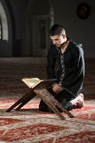 Muslim Man In Dishdasha Is Reading The Quran Royalty Free Stock Photo