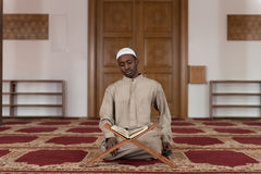 Muslim Man In Dishdasha Is Reading The Quran Royalty Free Stock Photography