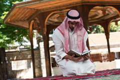 Muslim Man In Dishdasha Is Reading The Quran Royalty Free Stock Photos