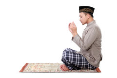 Muslim man doing prayer. Isolated over white background stock photo