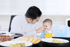 Muslim man feeding his baby. Young muslim men feeding his female baby with hand on the table at home Stock Photography