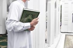 Muslim man hands holding the Koran Royalty Free Stock Photo