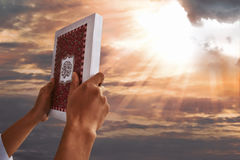 Muslim man hands holding koran. With sky background Stock Images