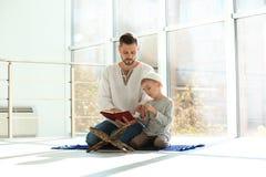 Muslim man and his son reading Koran together stock image