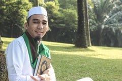 Muslim Man holding Al-Quran. In closeup shot Stock Images