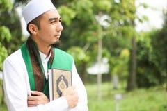 Muslim Man holding Al-Quran. In closeup shot Royalty Free Stock Image