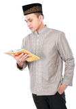 Muslim man holding and reading quran Royalty Free Stock Images