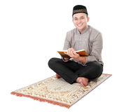Muslim man holding and reading quran Stock Photos