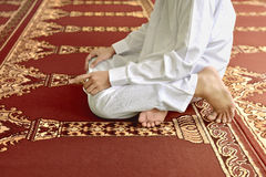 Muslim man kneeling while praying to god Stock Image