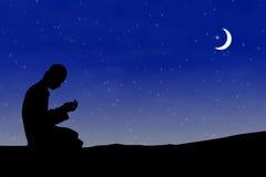 Muslim man praying. Silhouette muslim man praying at night with moon background during the month of ramadan Royalty Free Stock Photo