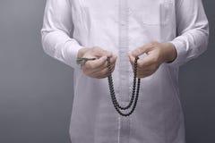 Muslim man praying with prayer beads Stock Photography