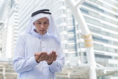 Muslim man praying in public place and modern building background Royalty Free Stock Images