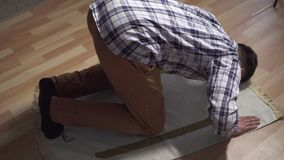 Muslim man sitting and praying with his hands up. Muslim man praying on rug in living room close up stock video