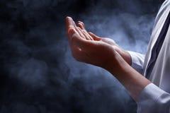 Muslim man praying. With smoke background Stock Photos