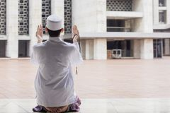 Muslim man praying to the Allah. Back view of a Muslim man holding beads while praying to the Allah and sitting in the mosque Stock Photography