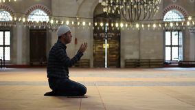Muslim man praying and worship at the mosque. Young adult caucasian muslim man praying and worship at the mosque stock video footage