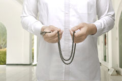 Muslim man raising hand and praying with prayer beads. Inside the mosque Stock Photo