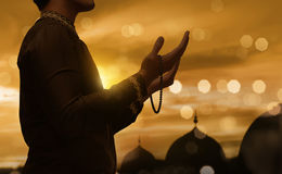 Muslim man raising hand and praying with prayer beads. During sunset background Stock Photos