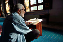 Muslim man reading the Holy Qur'an Stock Photos