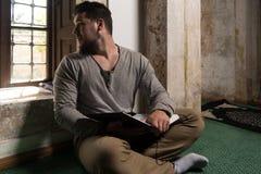 Muslim Man Is Reading The Koran Stock Photo