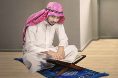 Muslim man reading Koran at home Stock Photos