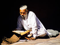 Muslim Man Reading the Koran. Senior muslim man dressed in white reading the Koran at a mosque. Delhi, India royalty free stock photo