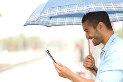 Muslim man reading a tablet under the rain stock image