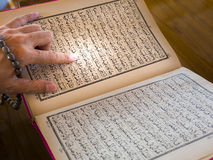 Muslim man's hand reading Quran Stock Images