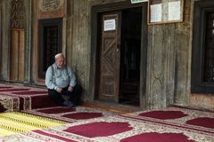 Muslim man seating in front mosque,Tetovo, Macedonia. Muslim man seating in front Aladza painted mosque,Tetovo, Macedonia royalty free stock photos