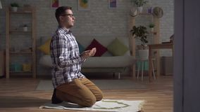 Muslim man sits in a prayer position, raising her hands and praying. In the living room stock footage