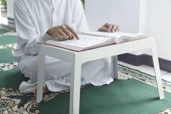 Muslim man sitting on carpet and reading the Koran Stock Image