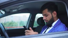 Muslim man sitting in the driver`s seat in the car and typing on the smartphone stock video